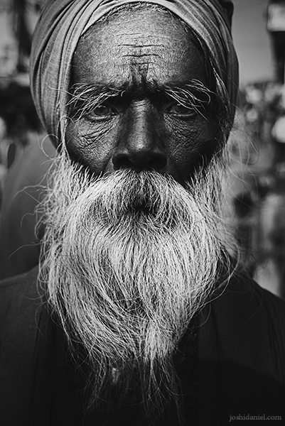 Black and white portrait of a sadhu in Varanasi with a deadpan expression